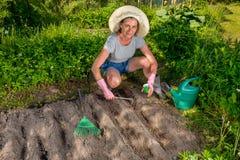 Frau, die Tasche von Samen und von Gartenwerkzeug hält Stockbild