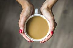 Frau, die Tasse Kaffee in ihren Händen hält Stockfotos