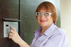 Frau, die Taste der Wechselsprechanlage eindrückt Stockbilder