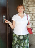 Frau, die Taste der Wechselsprechanlage eindrückt lizenzfreies stockbild