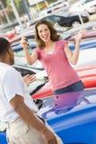 Frau, die Tasten zum neuen Auto aufhebt Lizenzfreie Stockfotografie