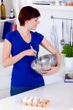 Frau, die Teig für einen Kuchen zubereitet und das receipe überprüft Stockbild