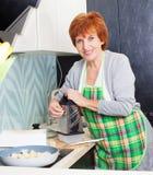Frau, die Teigwaren mit Käse zubereitet Lizenzfreies Stockfoto