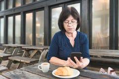 Frau, die Telefon auf Café im Freien betrachtet Lizenzfreie Stockfotografie
