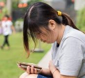 Frau, die Telefon auf Park verwendet Stockfoto