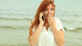 Frau, die am Telefon auf Strand, volles HD spricht stock footage