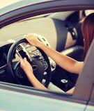 Frau, die Telefon beim Fahren des Autos verwendet stockfotografie