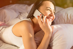 Frau, die am Telefon im Bett spricht stockbild