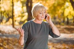 Frau, die am Telefon im Herbstpark spricht Lizenzfreie Stockfotos