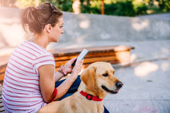 Frau, die Telefon im Park verwendet Stockbilder