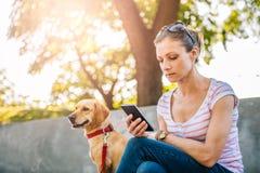 Frau, die Telefon im Park verwendet Lizenzfreie Stockfotografie