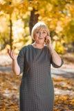 Frau, die am Telefon im unscharfen Hintergrund des Herbstparks spricht Stockbild