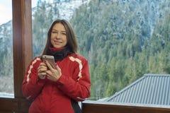 Frau, die am Telefon im Winterwald spricht stockfotografie