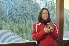 Frau, die am Telefon im Winterwald spricht lizenzfreie stockfotografie
