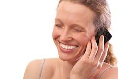 Frau, die am Telefon lächelt und spricht Stockfotografie
