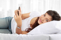 Frau, die am Telefon liegt auf Bett texting ist Stockfoto
