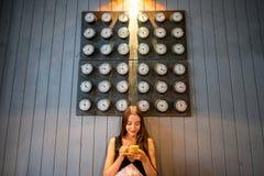 Frau, die Telefon mit vielen Uhren auf Hintergrund verwendet Lizenzfreie Stockfotos