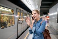Frau, die Telefonanruf an der Untertageplattform, bewegend macht wellenartig Stockfotos