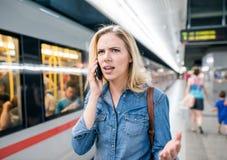 Frau, die Telefonanruf an der Untertageplattform, wartend macht Lizenzfreies Stockbild