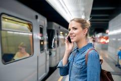 Frau, die Telefonanruf an der Untertageplattform, wartend macht Stockfotos