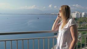 Frau, die Telefongespräch hat und Seeansicht vom Balkon genießt stock footage