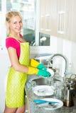 Frau, die Teller an der Küche tut Stockbild