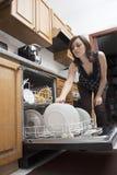 Frau, die Teller tut Stockbilder