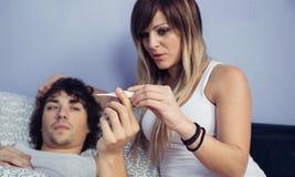 Frau, die Temperatur des kranken Mannes im Thermometer schaut Stockbilder
