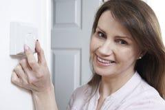 Frau, die Thermostat auf Zentralheizungs-Steuerung justiert Lizenzfreie Stockfotografie