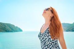 Frau, die tief einatmend Freiheit und gutes Wetter durch das Meer genießend lächelt Positive menschliche Gefühle, Gesichtsausdruc Stockfoto