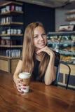Frau, die am Tisch mit einem Kaffeelächeln sitzt Stockfoto
