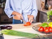 Frau, die Tomate auf Küche schneidet stockbilder