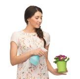 Frau, die Topf mit Blume und Sprühflasche hält Stockfotografie