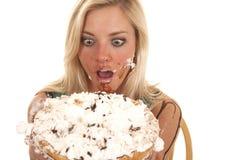 Frau, die Torte durch Gesicht unordentlich hält Stockbild