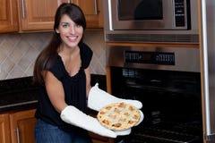 Frau, die Torte vom Ofen zieht Lizenzfreies Stockfoto