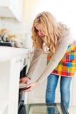 Frau, die Torte vom Ofen zieht Stockfotografie