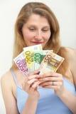 Frau, die trübselig einer Handvoll Geld betrachtet Stockfotos
