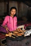 Frau, die traditionelles asiatisches Artlebensmittel an der Straße verkauft Luang Prabang, Laos Lizenzfreie Stockfotografie