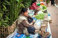 Frau, die traditionelles asiatisches Artlebensmittel an der Straße verkauft Luang Prabang, Laos Lizenzfreies Stockfoto