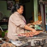 Frau, die traditionelles asiatisches Artlebensmittel an der Straße verkauft Luang Prabang, Laos Lizenzfreie Stockbilder