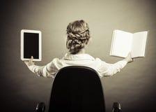 Frau, die traditionelles Buch und eBook Leser hält stockbild