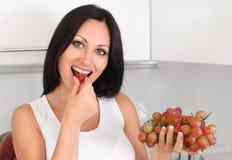 Frau, die Trauben isst stockbild
