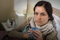 Frau, die trinkenden Tee der kalten Halsschmerzen trinkt lizenzfreie stockbilder