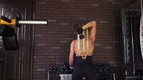 Frau, die Trizepsübung mit Dummköpfen tut Stockfoto