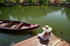 Frau, die tropische Ansicht am hölzernen Dock genießt lizenzfreie stockfotografie