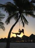 Frau, die am tropischen Strand schwingt lizenzfreie stockbilder