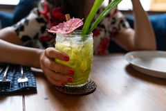 Frau, die tropisches grüne Farbcocktail in einem transparenten tiki Art-Cocktailglas hält stockfotografie