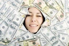 Frau, die trought Loch auf Geld bacground schaut Stockbild