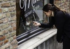 Frau, die um einer Katze sich kümmert stockfoto