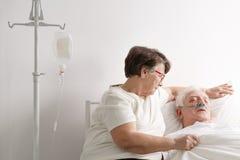 Frau, die um krankem Ehemann sich kümmert stockfotos